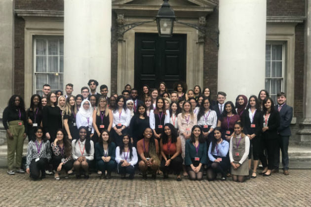 Group of over 30 interns outside a historical building.