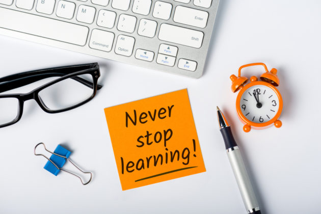 "Photograph of keyboard, glasses, paper clip, post-it note (which reads: ""never stop learning""), pen, and clock."