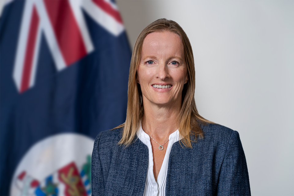 Woman smiling headshot with Cayman Islands flag in background.